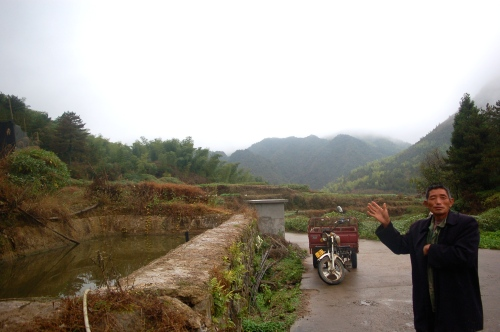 Beside the boundary marker, a local man indicates the land in Gaoping is protected from development
